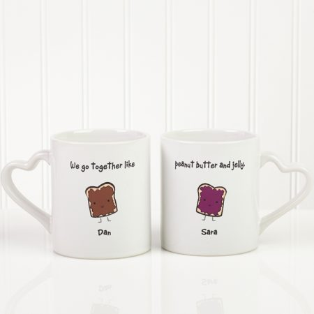 "Fun his and hers coffee mugs feature the saying ""We go together like peanut butter and jelly"" and are personalized with the couple's names. A fun and unique his and hers gift idea!"
