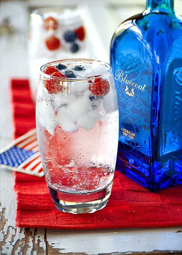 Jazz up a classic gin and tonic with raspberries and blueberries for a quick and easy 4th of July cocktail.